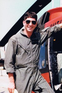 Young military airman Norm Massry in flight fatigues in front of a helicopter in flight school.